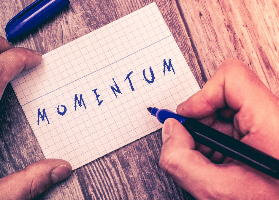 A mans hands writing the word momentum
